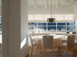 Imagen de estancia con mesas y sillas y ventanal exterior en Baqueira. Decoración e interiorismo obra del estudio de arquitectura e interiorismo Cristina Arechabala.