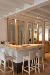 Imagen detalle de varias sillas de madera alrededor de una mesa en domicilio particular. Diseño de interiores obra del estudio de interiorismo y decoración Cristina Arechabala.