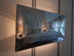 Imagen del dormitorio de una vivienda reflejado en una pieza metálica decorado por el estudio de interiores y diseño Cristina Arechabala.