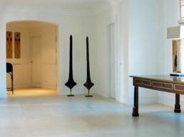 Imagen detalle de entrada con paredes blancas y obras de arte de diseño en domicilio particular. Trabajo del estudio de arquitectura y decoración Cristina Arechabala.