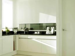 Imagen de cocina de lujo en colores claros y con ventana al exterior. Diseño de interiores y decoración por estudio de arquitectura e interiorismo Cristina Arechabala.