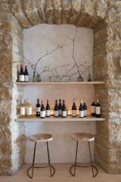 Imagen de una barra de bebidas y dos taburetes de diseño en piedra, hierro y madera diseñados por el estudio Cristina Arechabala.