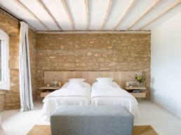 Imagen de un dormitorio en piedra y madera, con una cama y cojines blancos, decorado por el estudio Cristina Arechabala.